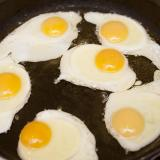 Six fried eggs in a pan with oil, for breakfast