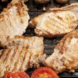 Grilled pork chops and tomatoes on a griddle