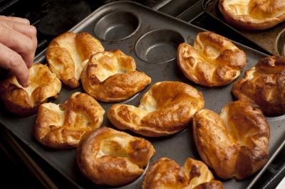 Man removing Yorkshire puddings from a baking tray